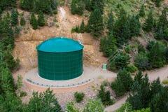 Tanque de armazenamento químico da grande água industrial verde na floresta de montes da montanha Foto de Stock