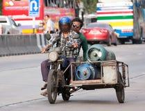 Tanque de gás dos carrys do side-car da motocicleta que conduz na rua fotografia de stock royalty free