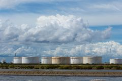 Tanques de óleo em seguido sob o céu azul, grande tanque industrial branco f Fotos de Stock Royalty Free