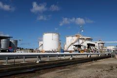 Tanques de armazenamento do gás e do combustível em uma refinaria de petróleo em um dia claro com céus azuis e as nuvens inchados foto de stock royalty free