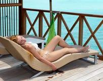 Tans van de vrouw op een terras van watervilla op oceaan royalty-vrije stock afbeelding