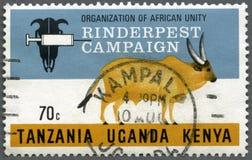 TANSANIA UGANDA KENIA - 1971: Shows Kampagnen-Emblem und Kuh, Reihe Rinderpestkampagne durch die Organisation für afrikanische Ei lizenzfreie stockfotos