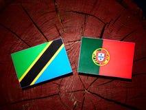 Tansanische Flagge mit portugiesischer Flagge auf einem Baumstumpf lokalisiert lizenzfreies stockbild
