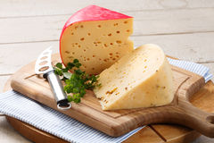 Gouda cheese and cheese knife on platter Royalty Free Stock Photos