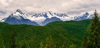 The Tantalus Mountain Range with the snow covered peaks of Alpha. Panoramic format photo of the Tantalus Mountain Range along the Sea to Sky Highway near Royalty Free Stock Photography