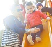 Tante en neefspel op de dia bij het park royalty-vrije stock fotografie