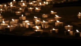Tantissime piccole candele rotonde bianche che bruciano nella sabbia Fondo delle candele brucianti della cera archivi video
