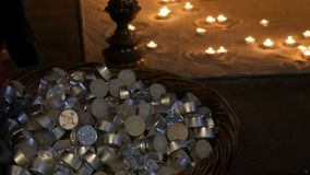 Tantissime piccole candele rotonde della cera che si trovano in un grande mucchio nelle candele brucianti del fondo archivi video