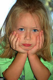 Tantrum kid. An angry caucasian blond girl toddler child portrait with disappointed expression in the face holding her head with her white hands and watching Royalty Free Stock Image
