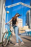 Tanya. bicycle city. Beautiful sensuality elegance lady. Brown woman. Happy fun cheerful smiling blue sunglasses black t-shirt jeans bicycle urban city portrait Royalty Free Stock Photo