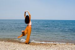 Tanz der jungen Frau auf dem Strand Lizenzfreies Stockfoto