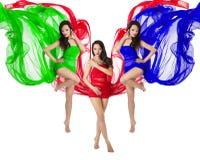 Tanz mit drei Frauen im roten, grünen, blauen Flugwesenkleid Stockfotografie