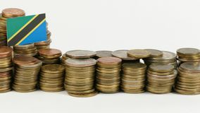 Tanzania flag with stack of money coins. Tanzania flag waving with stack of money coins stock video