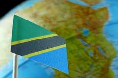 Tanzania flagga med en jordklotöversikt som en bakgrund Royaltyfri Foto
