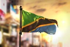 Tanzania flagga mot suddig bakgrund för stad på soluppgång Backlig Arkivfoto