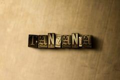 TANZANIA - närbild av det typsatta ordet för grungy tappning på metallbakgrunden Arkivbild