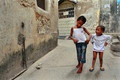 Tanzania Zanzibar, stenstad, två mörkhyade flickor som spelar I Arkivfoton