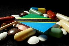 Tanzaniaanse vlag met partij van medische die pillen op zwarte backg wordt geïsoleerd Stock Foto's