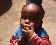 Tanzanian baby. Portrait Tanzanian child who licks his fingers after candy Stock Photography