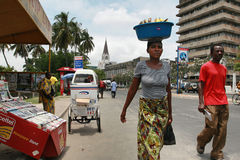 Tanzanian black African woman carries cargo on your head. Stock Photos