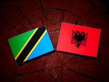 Tanzanian flag with Albanian flag on a tree stump isolated royalty free illustration