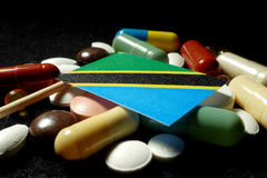Tanzanian flag with lot of medical pills isolated on black backg Stock Photos