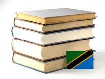 Tanzanian flag with pile of books isolated on white background. Tanzanian flag with pile of books isolated on white Stock Photos