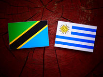 Tanzanian flag with Uruguaian flag on a tree stump isolated royalty free stock images