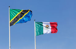 Tanzanian and Mexican flags. The national flags of Tanzania left and Mexico right hoisted agianst a blue sky Stock Photography