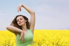 Tanzen der jungen Frau auf dem Rapsblumengebiet Lizenzfreies Stockfoto