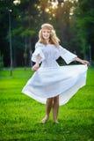 Tanzen der jungen Frau auf grünem frischem Gras in einem Park Lizenzfreie Stockbilder