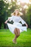 Tanzen der jungen Frau auf grünem frischem Gras in einem Park Lizenzfreie Stockfotos