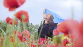 Tanzen der jungen Frau des Porträts in einer Mohnblumenfeld-Holdingflagge von Ukraine in den Händen draußen Verbindung mit Natur stock video