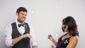 Tanzen des glücklichen Paars in den Seifenblasen an der Partei stock footage