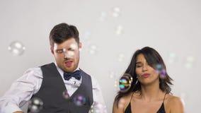 Tanzen des glücklichen Paars in den Seifenblasen an der Partei stock video footage