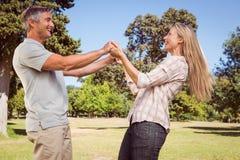 Tanzen des glücklichen Paars im Park Stockfotografie