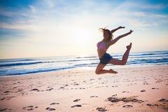 Tanzen des jungen Mädchens am Strand am Hintergrund des blauen Himmels Lizenzfreie Stockfotografie