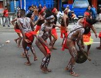 Tanzen Papuanmänner und Frauen in der traditionellen Kleidung und Gesichtsmalereien von Kaimana Lizenzfreie Stockbilder