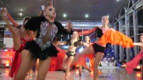 Tanzen Sie Wettbewerb, schöne Mädchen in die schönen Kostüme, die sich synchron in Autosalon bewegen stock footage