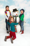 Tanzen um den Schneemann Lizenzfreie Stockbilder
