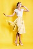 Tanzende blonde Frau im gelben Rock Lizenzfreie Stockbilder