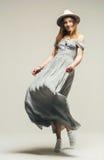 Tanzende blonde Frau im grauen Kleid und im Hut Stockbilder