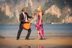 Tanzende blonde Zurückansicht und Gitarrist auf Strand Stockbild