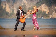 Tanzende blonde Zurückansicht und Gitarrist auf Strand Stockfotos