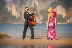 Tanzende blonde Zurückansicht und Gitarrist auf Strand Lizenzfreie Stockfotografie