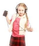 Tanzende Kopfhörermusik des kleinen Mädchens, die auf weißem Hintergrund singt Lizenzfreie Stockfotos
