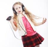 Tanzende Kopfhörermusik des kleinen Mädchens, die auf weißem Hintergrund singt Stockbilder