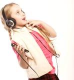 Tanzende Kopfhörermusik des kleinen Mädchens, die auf weißem Hintergrund singt Lizenzfreies Stockbild