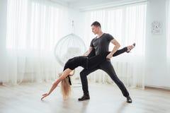 Tanzende lateinische Musik der jungen Paare: Bachata, merengue, Salsa Haltung der Eleganz zwei auf Reinraum Stockbild