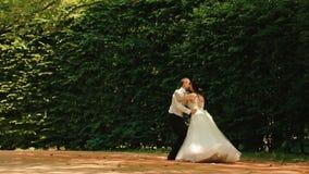 Tanzende reizend Paare von Jungvermählten im schönen grünen Park Hübscher Bräutigam hebt sie an und spinnt um herein stock video